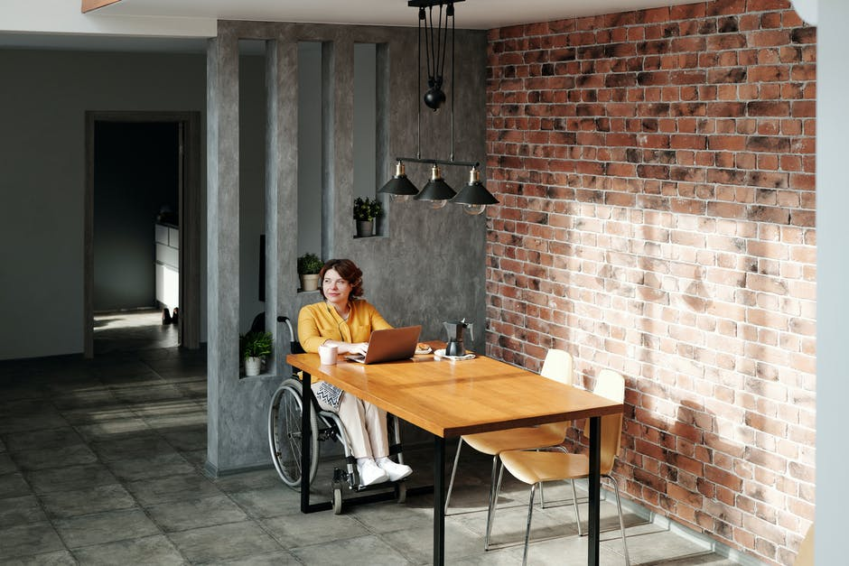 A person sitting in a chair in front of a brick building